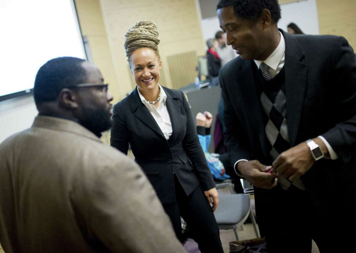 FILE - In this Friday, Jan. 16, 2015, file photo, Rachel Dolezal, center, Spokane's newly-elected NAACP president, smiles as she meets with Joseph M. King, of King's Consulting, left, and Scott Finnie, director and senior professor of Eastern Washington University's Africana Education Program, before the start of a Black Lives Matter Teach-In on Public Safety and Criminal Justice, at EWU, in Cheney, Wash. Dolezal's family members say she has falsely portrayed herself as black for years. (Tyler Tjomsland/The Spokesman-Review via AP, File)