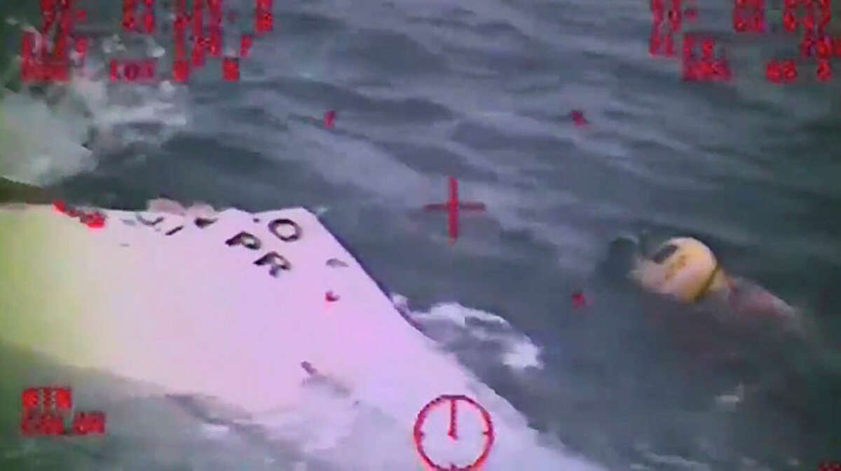 In this Sunday, Oct. 4, 2015 photo made from video and released by the U.S. Coast Guard, a Coast Guard crew member investigates a life boat, that was found from the missing ship El Faro. On Monday, four days after the ship vanished, the Coast Guard concluded it sank near the Bahamas in about 15,000 feet of water. One unidentified body in a survival suit was spotted, and the search went on for any trace of the other crew members. The search continued Tuesday, Oct. 6, 2015.
