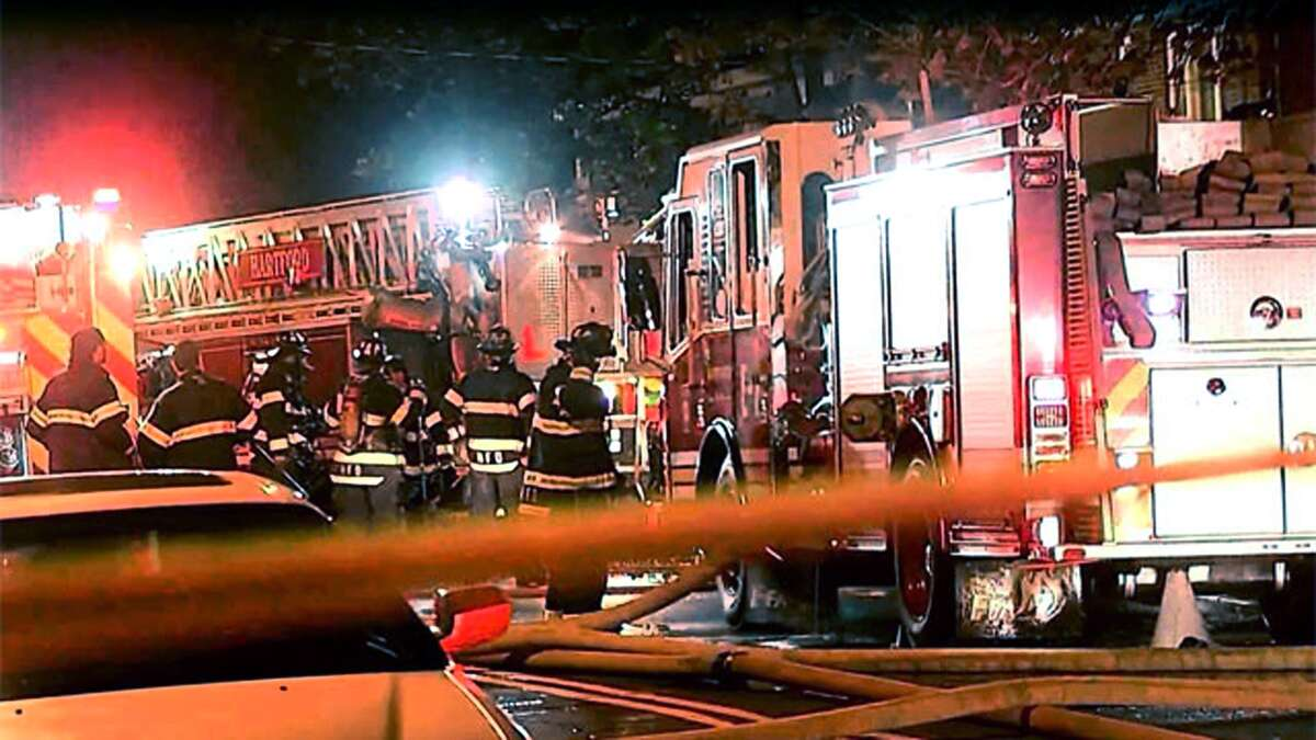 Firefighters man an engine at the scene of a two-alarm blaze, where a firefighter died and three others injured, at a house fire Tuesday night in Hartford.
