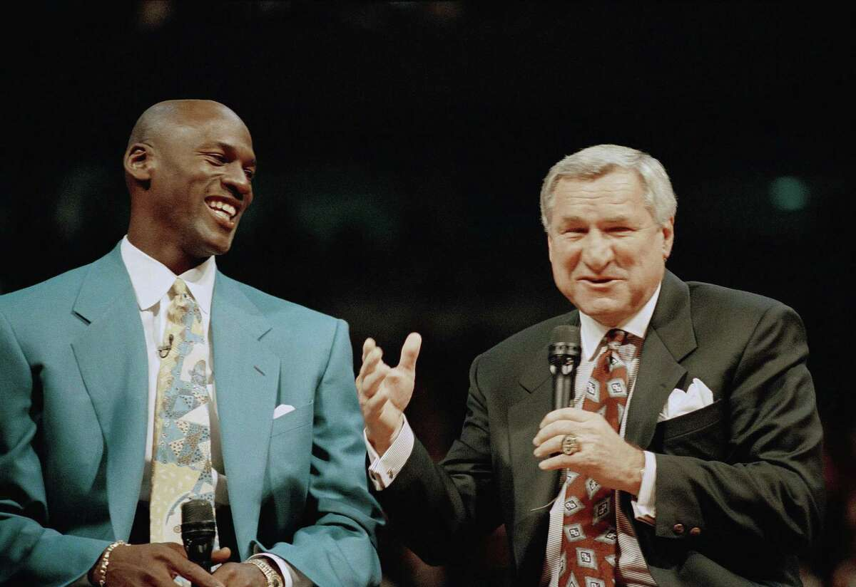"""Former Chicago Bulls great Michael Jordan, left, shares a moment with Dean Smith, his former coach at North Carolina, during ceremonies honoring Jordan at Chicago's United Center. Smith, the North Carolina basketball coaching great who won two national championships, died """"peacefully"""" at his home Saturday night the school said in a statement Sunday from Smith's family. He was 83."""