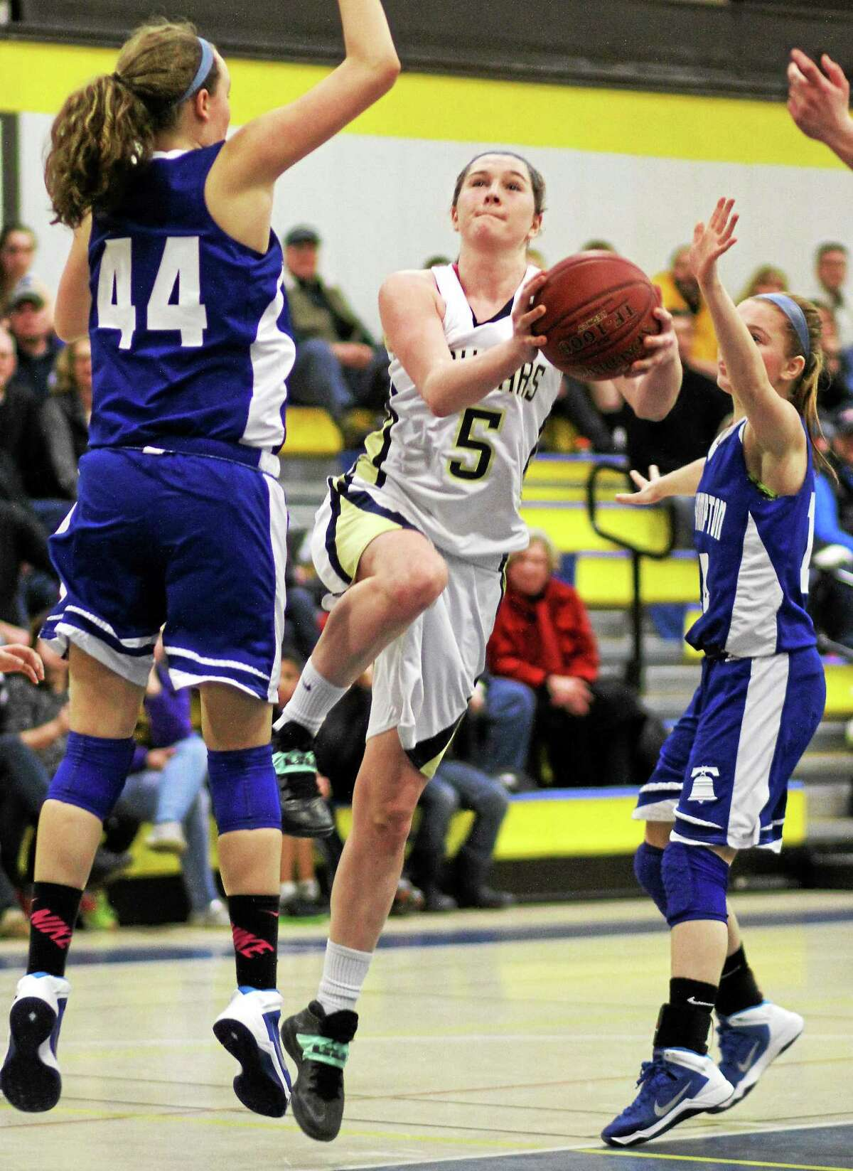Haddam-Killingworth senior Lauren McCann (5) makes her move while East Hampton's Sarah Massie (44) looks to defend in Saturday's SLC quarterfinal contest. McCann had 17 points to lead the Cougars to Tuesday's semifinals.