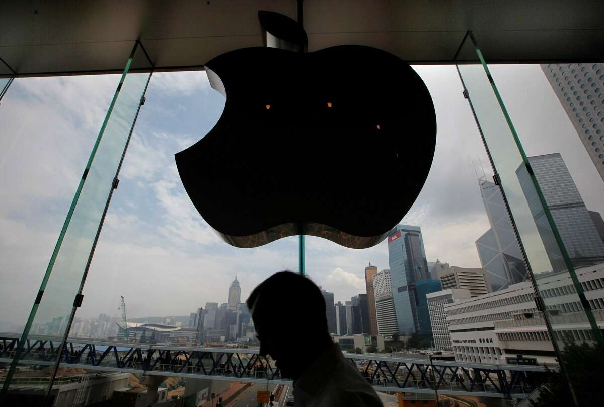 A customer walks past an Apple logo at an Apple Store in Hong Kong.