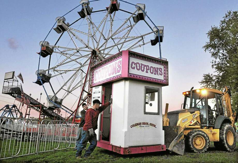 Don Michaels, an employee of Coleman Bros. Shows, and Erick Johnson, a Portland Fair volunteer, guide Mike Lastrina, the director of grounds maintenance at the fair as he transports one of three ticket booths in the carnival midway using a payloader in this October 2010 file photo. Photo: Catherine Avalone - The Middletown Press  / TheMiddletownPress