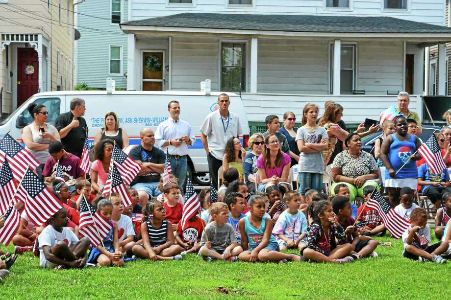 Macdonough school staff, parents, teachers and community members pay tribute to the American Flag on Friday. It's a colorful and musical tradition at Middletown's North End elementary. Photo: Photos By Brian Zahn — The Middletown Press