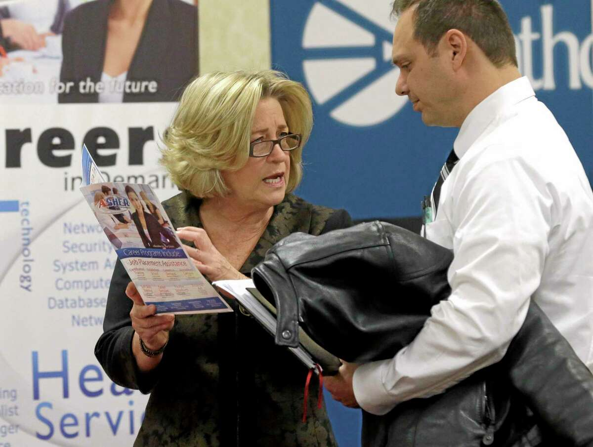 In this Jan. 22, 2014, file photo, recruiter Valera Kulow, left, speaks with job seeker Leonardo Vitiello during a career fair in Dallas.
