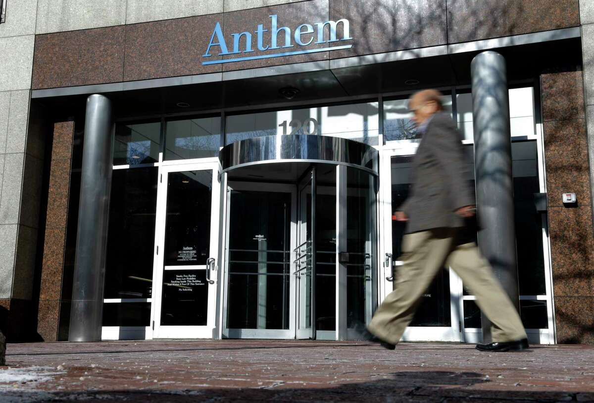 A man walks past health insurer Anthem's corporate headquarters in Indianapolis.
