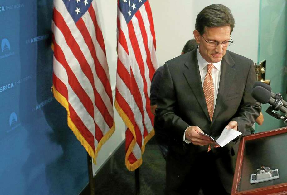 House Majority Leader Eric Cantor of Va. takes the podium to speak to reporters on Capitol Hill in Washington, Wednesday, June 11, 2014, after a House Republican caucus meeting. Repudiated at the polls, House Majority Leader Eric Cantor intends to resign his leadership post at the end of next month, officials said Wednesday, clearing the way for a potentially disruptive Republican shake-up just before midterm elections with control of Congress at stake.  (AP Photo/Charles Dharapak) Photo: AP / AP