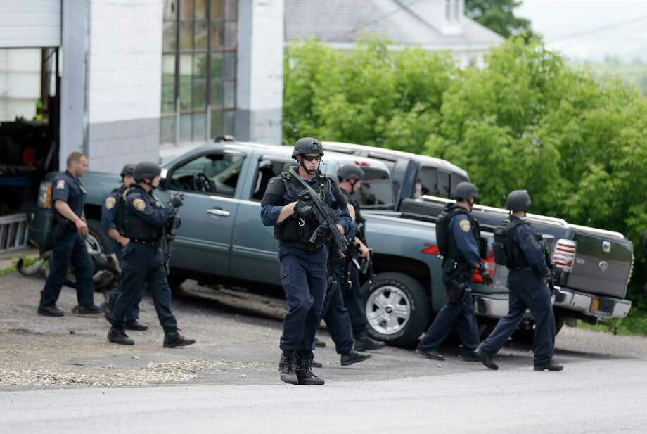 Law enforcement officials walk the streets near the prison in Dannemora, N.Y. on June 10, 2015. Police were resuming house-to-house searches near the maximum-security prison in northern New York where two killers escaped using power tools, authorities said Wednesday as they renewed their plea for help from the public. Photo: AP Photo/Seth Wenig  / AP
