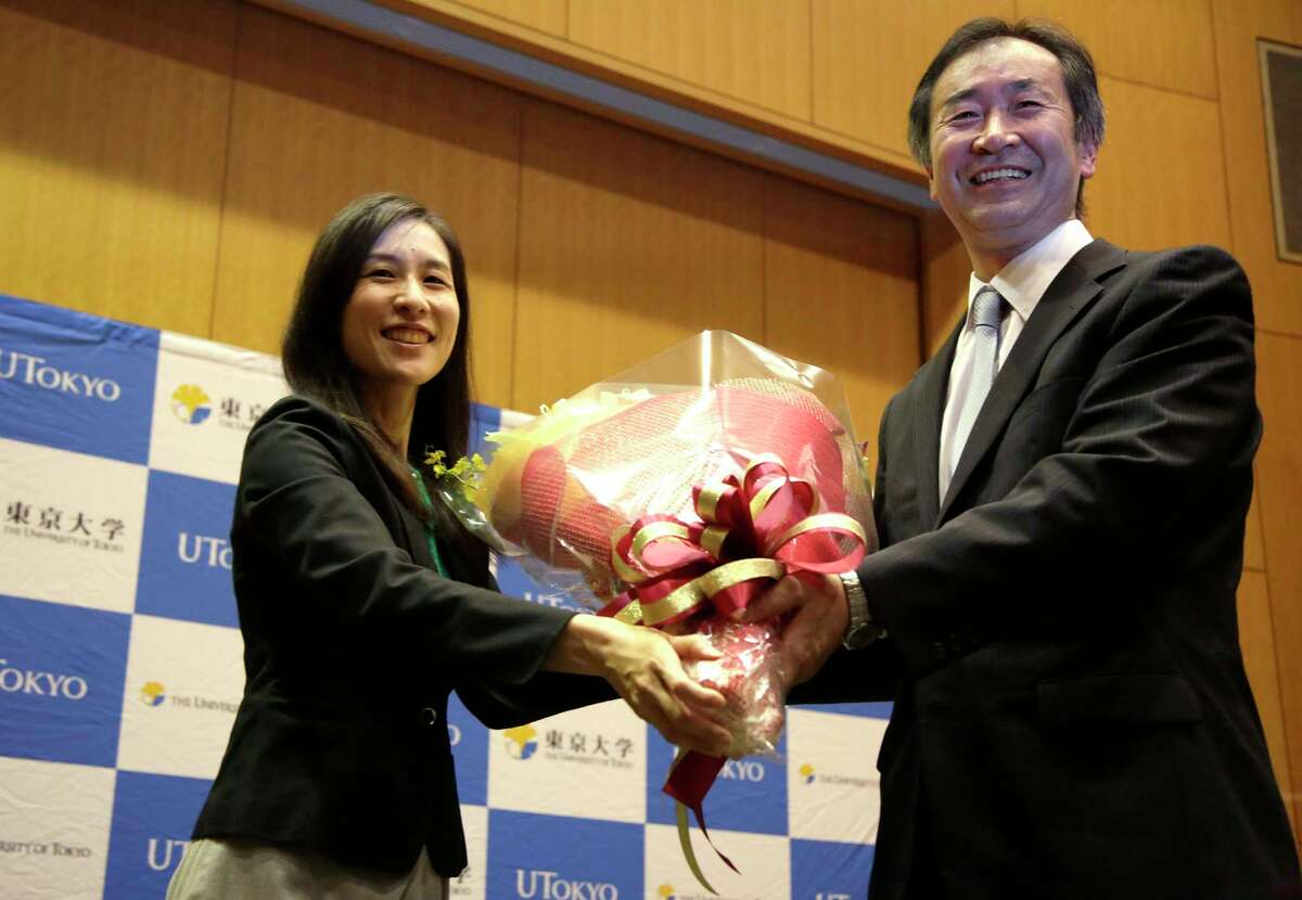 Takaaki Kajita of Japan, right, director of the Institute for Cosmic Ray Research and professor at the University of Tokyo, receives flower during a press conference after learning he won the Nobel Prize in physics at the university in Tokyo on Oct. 6, 2015. Kajita and Arthur McDonald of Canada won the Nobel Prize in physics on Tuesday, for the discovery of neutrino oscillations.