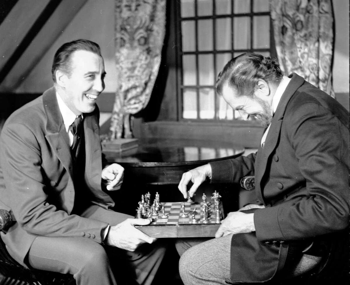 FILE - In this file photo dated Dec. 17,1968, British actor Christopher Lee, left and American actor Vincent Price, share a joke whilst playing chess during a break in the filming of Edgar Allen Poe's