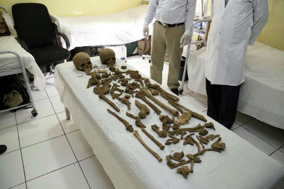 In this image provided by the Afghan Presidential Palace, Monday, Oct. 6, 2015, parts of two human skeletons are seen that were found in the vicinity of Palace No. 1 in the presidential palace compound. Afghanistan's president palace says skulls and bones belonging to two bodies have been uncovered beneath a kitchen during renovation work on the palace grounds. The gender, cause of death and identity of the skeletons are a mystery. (Afghan Presidential Palace via AP) Photo: AP / Presidential Palace
