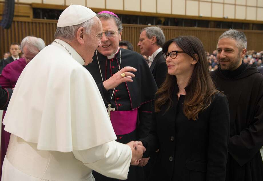 FILE -- In this file photo taken at the Vatican, on Feb. 4, 2015, Pope Francis shakes hands with Italian lawyer Lucia Annibali during the weekly general audience in the Pope Paul VI hall, . Annibali, became a symbol in the fight against men's violence toward women, after suffering in the 2013 an acid attack masterminded by her ex-boyfriend Luca Varani, also a lawyer. Varani has been convicted and sentenced to 20 years in prison for ordering the attack on his ex-girlfriend. Two Albanian men were convicted of throwing the acid and each received a 14 year term. On saturday in a speech, Francis decried disfiguring attacks on women. (AP Photo/L'Osservatore Romano, Pool) Photo: AP / L'Osservatore Romano