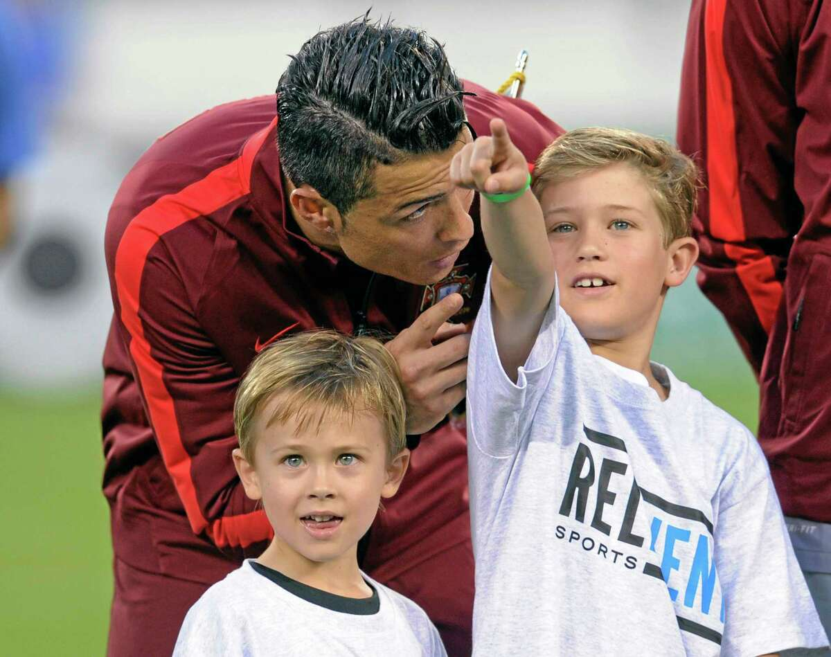 Portugal's Cristiano Ronaldo talks to the children who escorted him out to the pitch before an international friendly against the Republic of Ireland on Tuesday in East Rutherford, New Jersey.