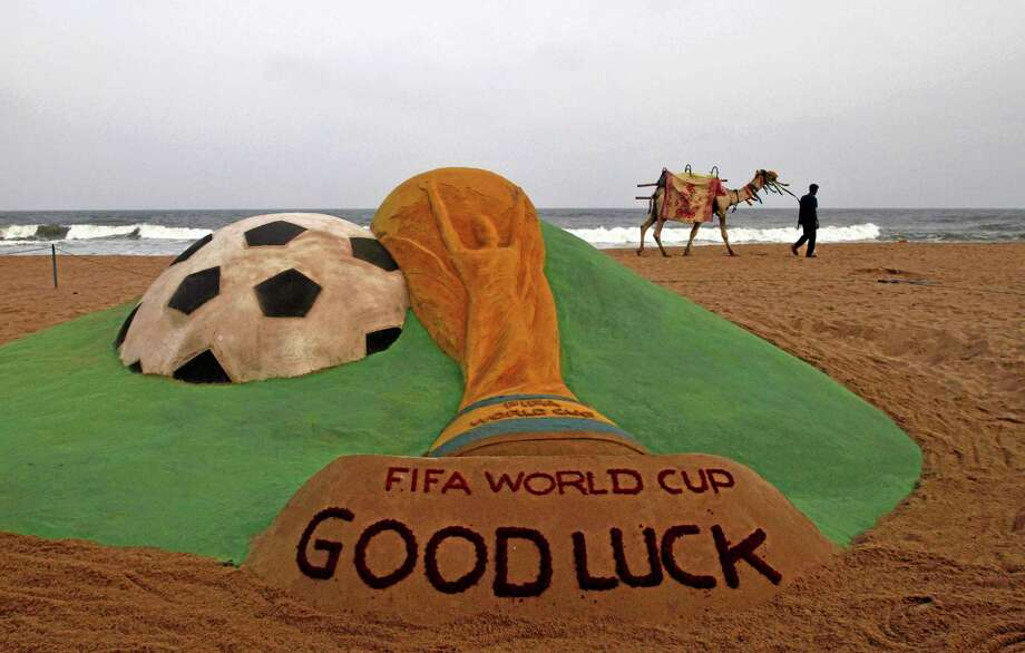 A camel joy ride hawker walks Wednesday past a FIFA World Cup 2014 sand sculpture created by Indian sand artist Sudarshan Pattnaik on the Bay of Bengal coast in Puri, Orissa, India. Photo: Biswaranjan Rout — The Associated Press  / AP