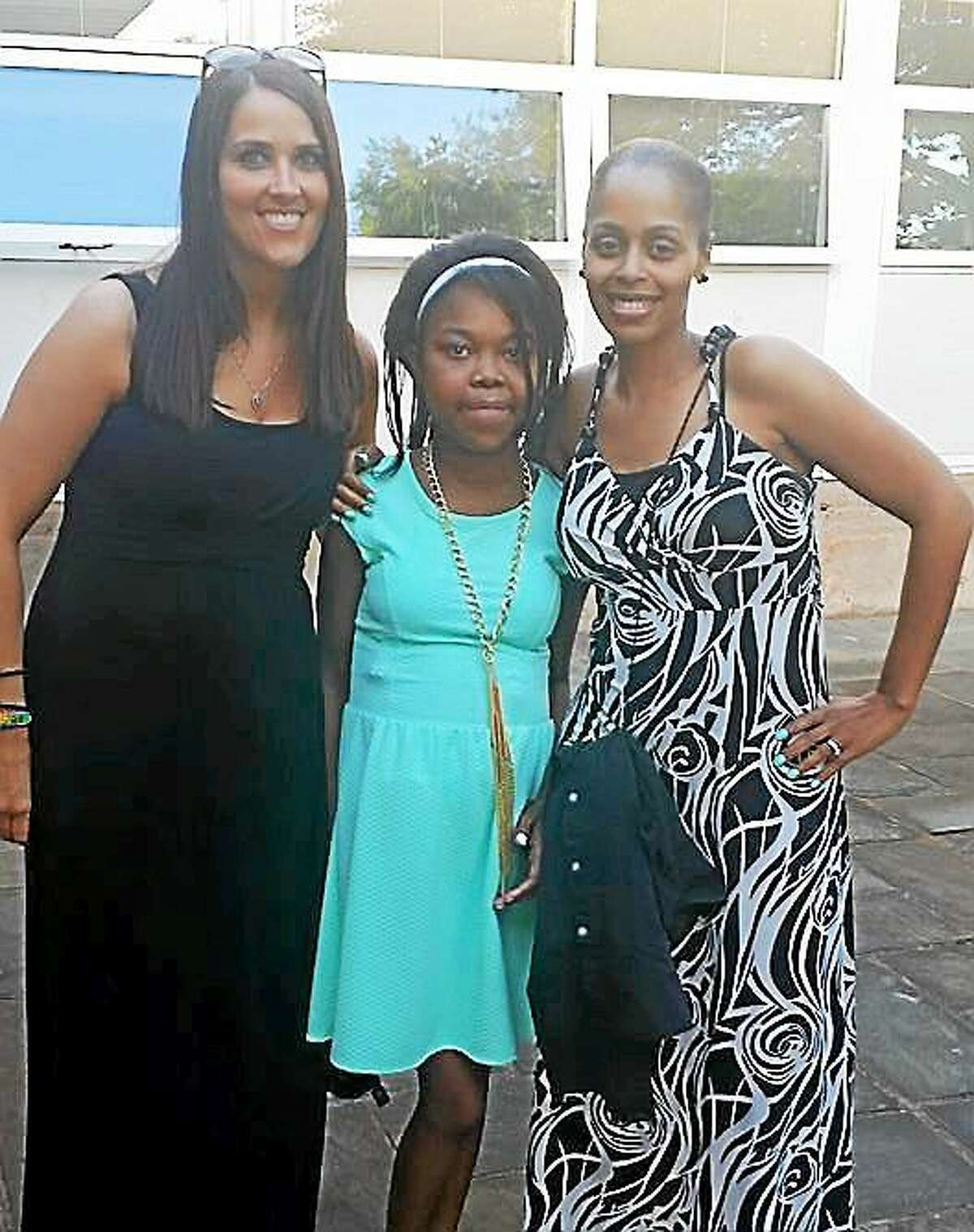 "Woodrow Wilson Middle School teachers Meghan Mahon and Shelia Morris pose with Navaiah at the dance last Friday. Both teachers have kept in touch with the family, ""almost on a daily basis"" since day one, the family said."