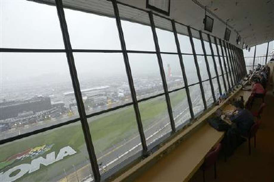 Reporters watch from the press box as heavy thunderstorms move through the area during the NASCAR Daytona 500 auto race at Daytona International Speedway in Daytona Beach, Fla., Sunday, Feb. 23, 2014. (AP Photo/Phelan M. Ebenhack) Photo: AP / FR121174 AP