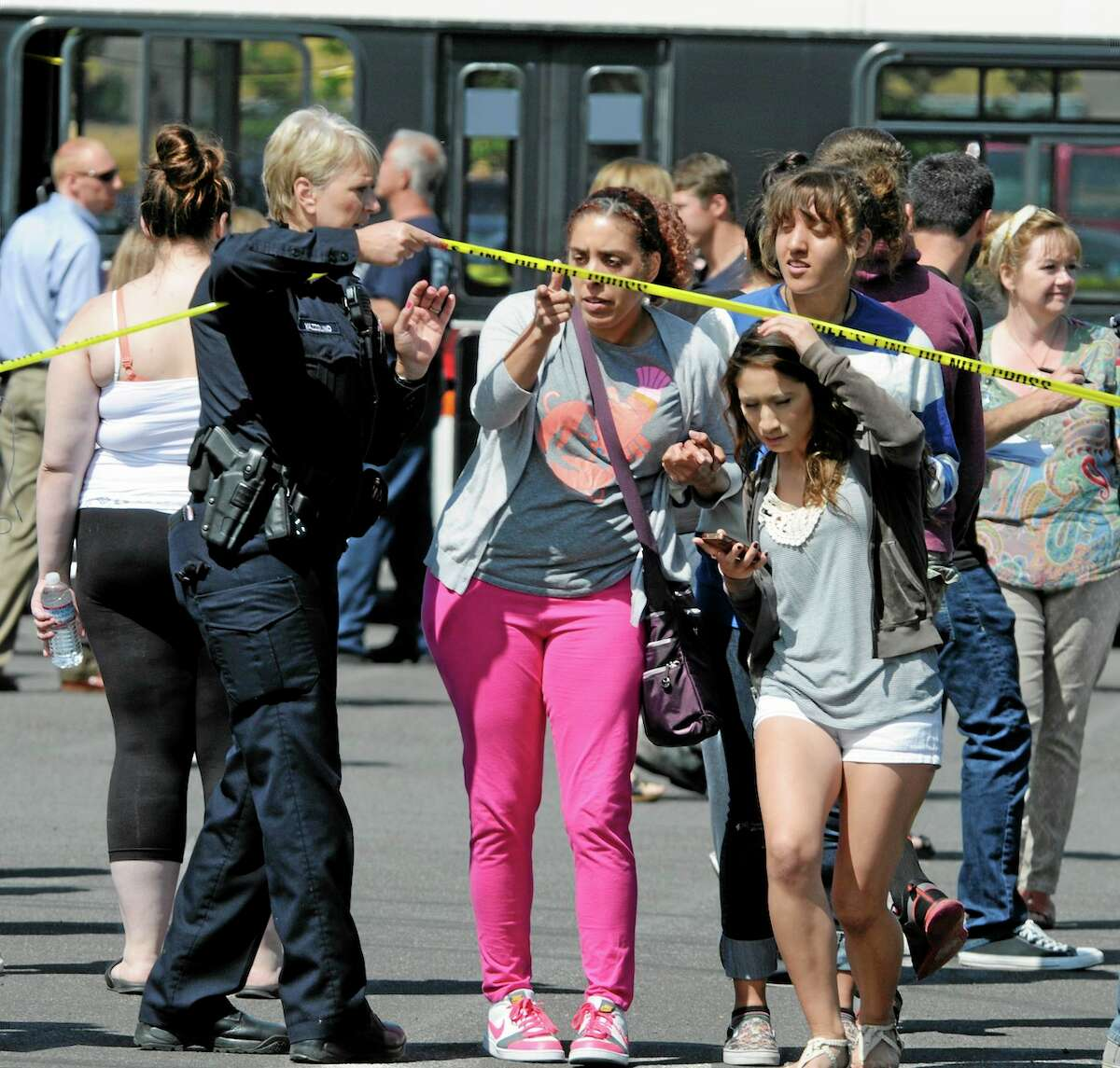 A police officer lifts up police tape as students are arrive by bus to meet their parents and/or family at the Fred Meyer grocery store parking lot in Wood Village, Ore., after a shooting at Reynolds High School Tuesday, June 10, 2014, in nearby Troutdale. A gunman killed a student at the high school east of Portland Tuesday and the shooter is also dead, police said. (AP Photo/Greg Wahl-Stephens)