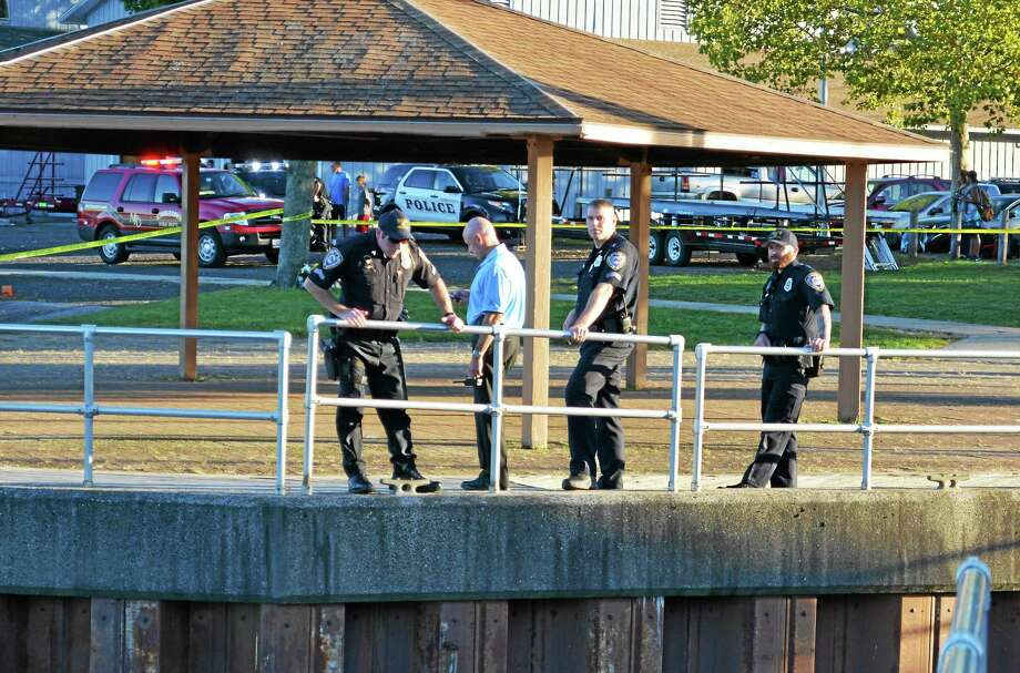 Middletown police officers stand along the railing at Harbor Park. The entire area from the boathouse to the boardwalk at the rear entrance of the Mattabesett Canoe Club was cordoned off with police tape Tuesday evening. Photo: Cassandra Day — The Middletown Press