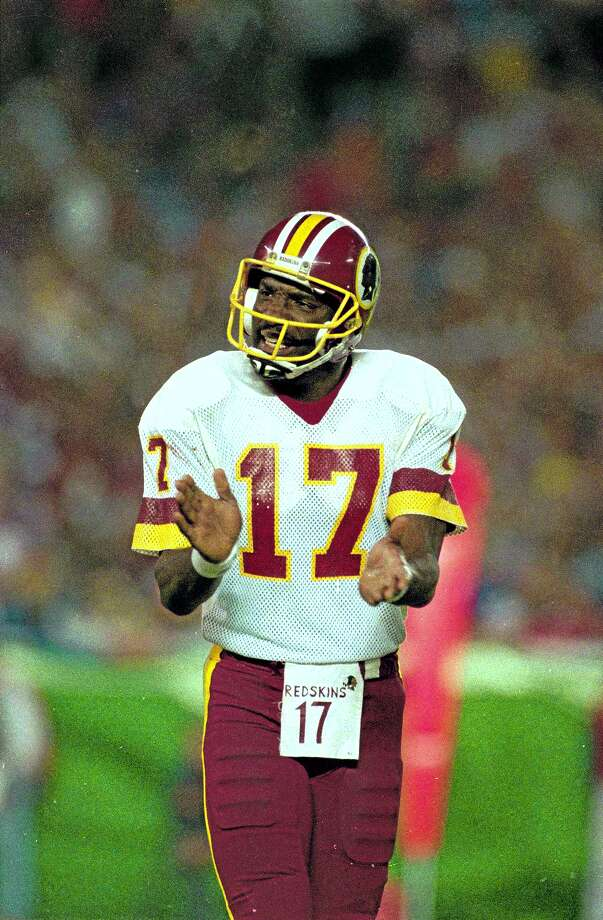 FILE - In this Jan. 31, 1988, file photo, Washington Redskins quarterback Doug Williams cheers his team on during the third quarter of the Super Bowl against the Denver Broncos in San Diego. Williams is coming back to the Redskins to work in the front office. The Redskins announced Monday, Feb. 10, 2014, that the quarterback who led the team to the Super Bowl championship in the 1987 season will serve as a personnel executive. (AP Photo/Amy Sancetta) (AP Photo/Amy Sancetta, File) Photo: AP / AP
