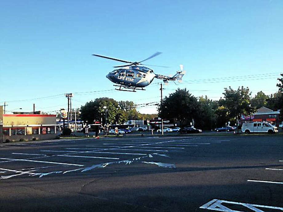 LifeStar landed in the Burger King parking lot on Berlin Road in Cromwell on Tuesday afternoon to take a motorcycle rider to Hartford Hospital after an accident. Photo: Jeff Mill — The Middletown Press