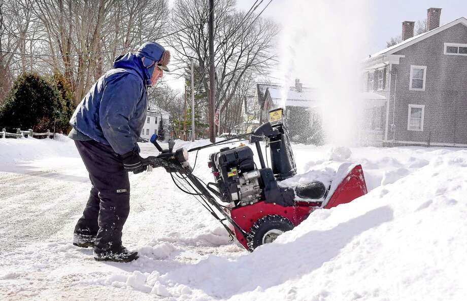 Jesus Barrera clears snow from in front of a home on West River Street in Milford earlier this month. Photo: (Arnold Gold-New Haven Register)