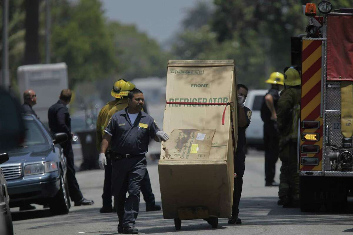 FILE - In this July 9, 2010, file photo, Los Angeles Police assistants take away a refrigerator, as investigators gather evidence at the home of suspect Lonnie David Franklin Jr. in Los Angeles. Franklin was arrested July 7, 2010, on 10 counts of murder, one count of attempted murder and special circumstance allegations of multiple murders that could make him eligible for the death penalty. Relatives of victims will urge a Los Angeles Superior Court judge Friday, Feb. 6, 2015, to set a trial date for Franklin, who is charged with 10 counts of murder, and has been dubbed the