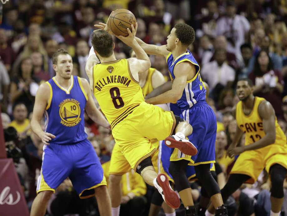Cavaliers guard Matthew Dellavedova makes a shot and is fouled by Golden State Warriors guard Stephen Curry during the fourth quarter of Game 3 of the NBA Finals on Tuesday in Cleveland. Photo: Tony Dejak — The Associated Press  / AP