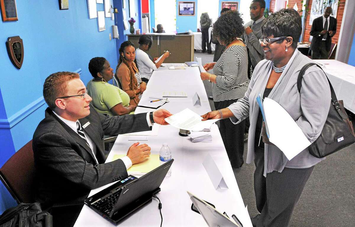 In this file photo, Madelyn Robinson of New Haven hands her resume off to Grant Faber, a human resources rep from Omni Hotel & Resorts, during the STRIVE Career Resource fair. Around 200 job seekers sought employment opportunities from 14 local employers at the event. (Peter Casolino — New Haven Register)