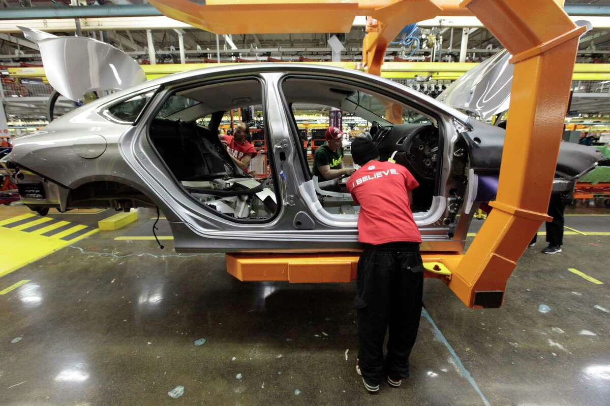 In this March 14, 2014, photo, assembly line workers build a 2015 Chrysler 200 automobile at the Sterling Heights Assembly Plant in Sterling Heights, Mich.