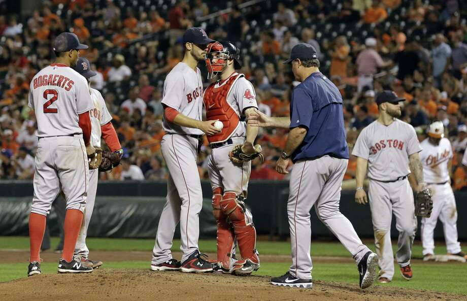 Red Sox starter Rick Porcello hands the ball to manager John Farrell as he is removed during the sixth inning of Boston's 5-2 loss to the Orioles on Wednesday in Baltimore. Photo: Patrick Semansky — The Associated Press  / AP