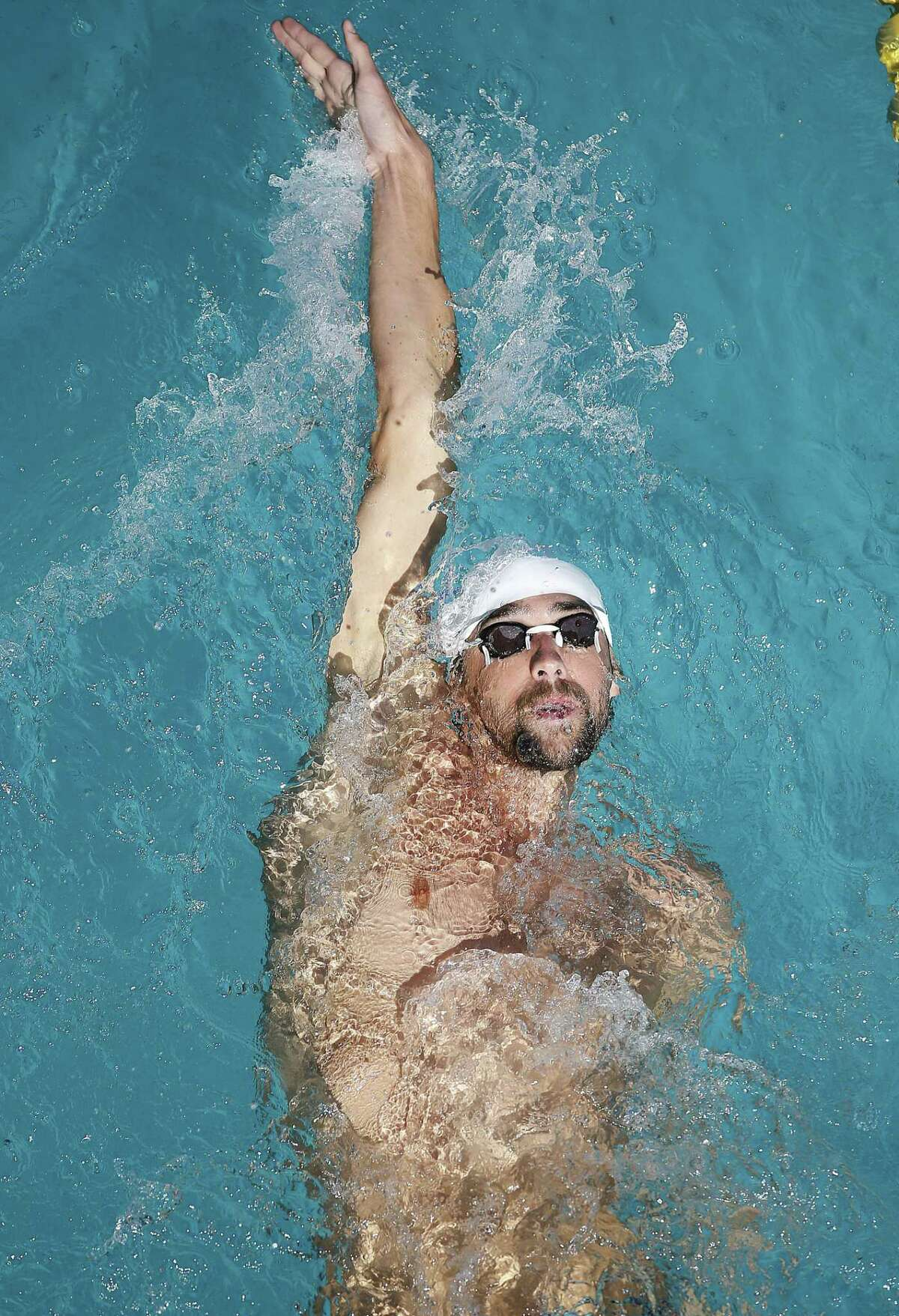 FILE - In a June 22, 2014, file photo Michael Phelps swims in the warm up pool during the Santa Clara International Grand Prix swim meet in Santa Clara, Calif. USA Swimming on Monday, Oct. 6, 2014, suspended Phelps for six months as a result of the Olympic champion's second DUI arrest.