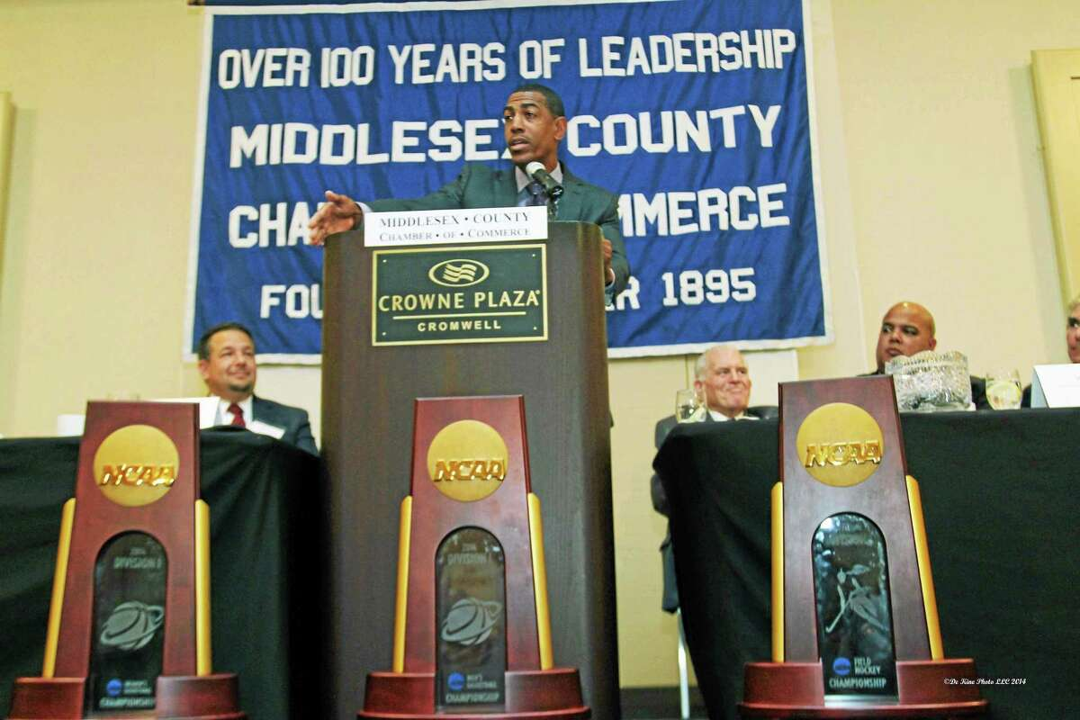 UConn Head Men's Basketball Coach Kevin Ollie addresses a sold-out Middlesex County Chamber of Commerce member breakfast Oct. 1 in Cromwell as Chairman Rich Carella, President Larry McHugh and UConn Director of Athletics Warde Manuel look on.