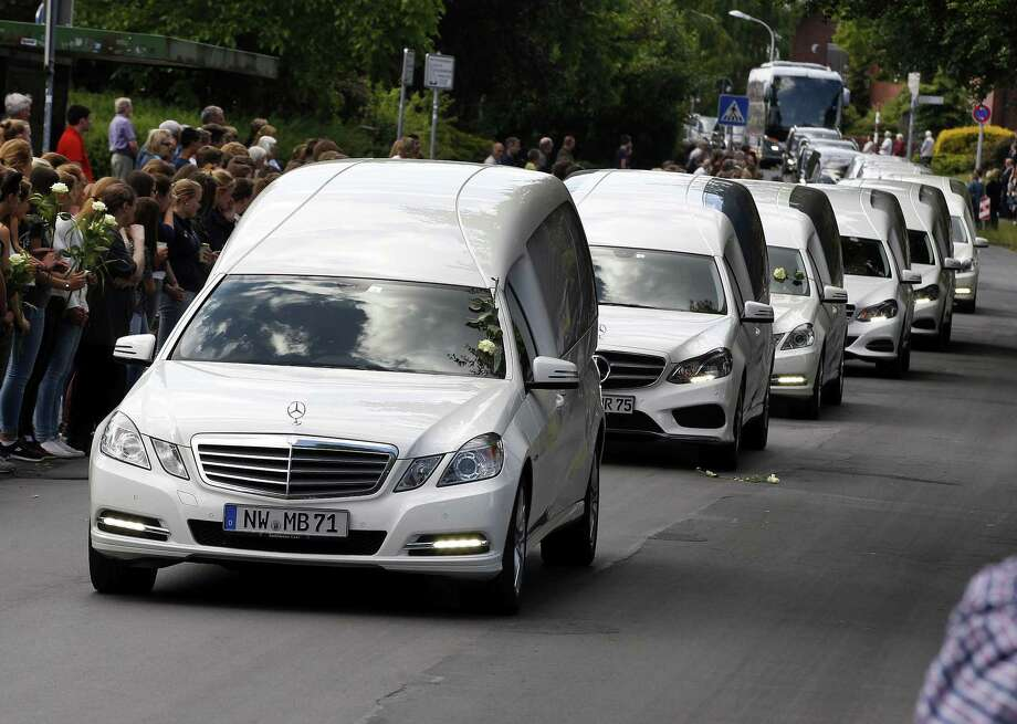 White hearses carrying the remains of pupils killed in the Germanwings plane crash in France are about to pass by the Joseph-Koenig high school in Haltern, Germany, Wednesday, June 10, 2015. 150 people died in the plane crash on March 24. (AP Photo/Michael Probst) Photo: AP / AP