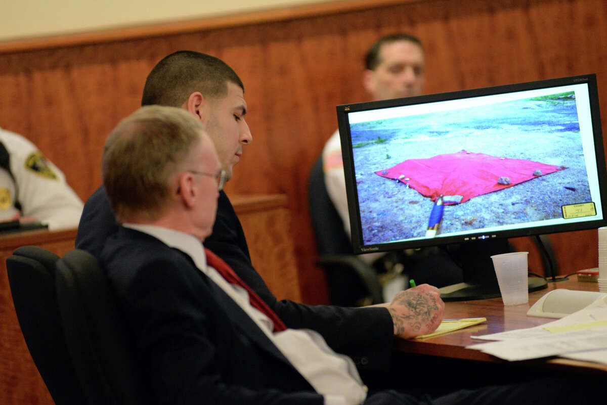 Former New England Patriot Aaron Hernandez takes notes next to his attorney, Charles Rankin, as a photo of the covered body of Odin Lloyd is displayed on a screen during his murder trial Thursday at Bristol County Superior Court in Fall River, Mass.