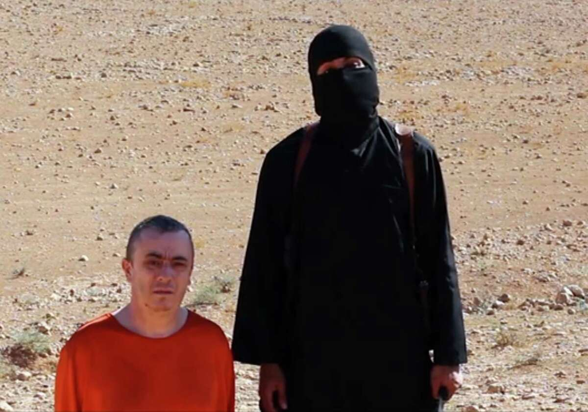 This undated image shows a frame from a video released Friday, Oct. 3, 2014, by Islamic State militants that purports to show the killing of journalist Alan Henning by the militant group. Internet video released Friday purports to show an Islamic State group fighter beheading British hostage Alan Henning and threatening yet another American captive, the fourth such killing carried out by the extremist group now targeted in U.S.-led airstrikes.