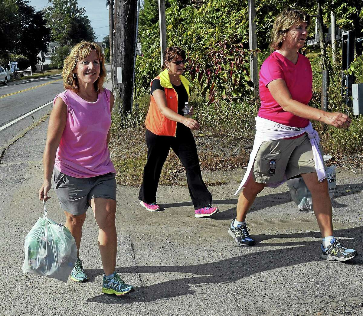 In this Sept. 21, 2014 photo, Deb McGowan of North Stonington, Conn., left, walks along U.S. Route 3 while picking up recyclables with friends Tracy Stedman, center, Linda Stefanski, right, in Ashaway, R.I., Over the past year, McGowan, 47, has redeemed 10,000 beverage containers to raise her $500 fundraising commitment for the ninth annual Terri Brodeur Breast Cancer Foundation Walk Across Southeastern Connecticut.