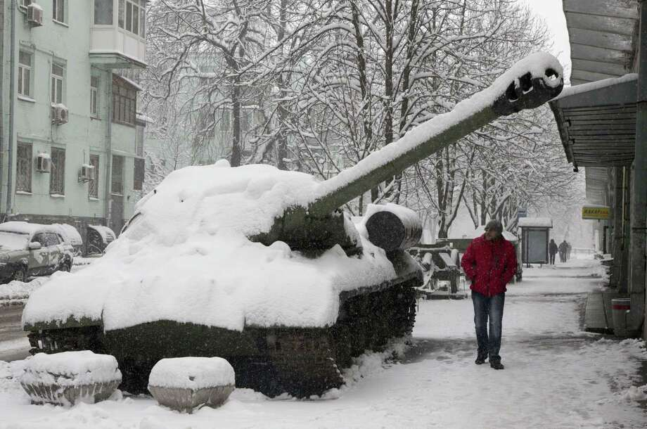 People pass by a tank in Kiev that has been used by pro-Russian separatists in the country's east and then brought to the Ukrainian capital as a symbol of the current conflict, Thursday, Feb. 5, 2015. The Ukrainian government is anxious to use Thursday's visit by U.S. Secretary of State John Kerry to Kiev to reiterate its plea for lethal aid. President Barack Obama has opposed the idea of sending weapons to Ukraine but sources in his administration say this position could change in the light of recent events.  (AP Photo/Efrem Lukatsky) Photo: AP / AP