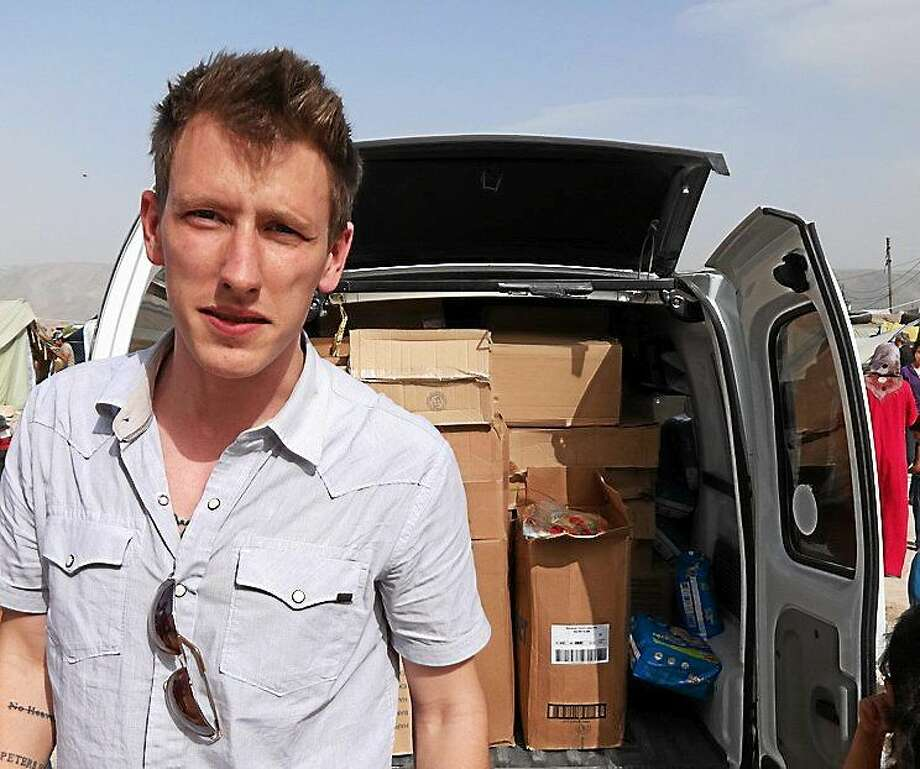 This undated photo provided by Kassig Family shows Peter Kassig standing in front of a truck filled with supplies for Syrian refugees. A video purportedly produced by militants in Syria released on Oct. 3, 2014, shows Kassig, of Indianapolis, kneeling on the ground as a masked militant says he will be killed next. Photo: AP Photo/Courtesy Kassig Family  / Kassig Family