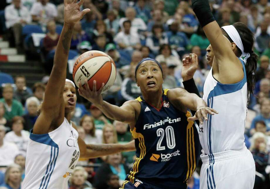 The Indiana Fever's Briann January, center, attempts a layup between the Lynx's Rebekkah Brunson, left, and Maya Moore in the first half Sunday. Photo: Jim Mone —  The Associated Press  / AP