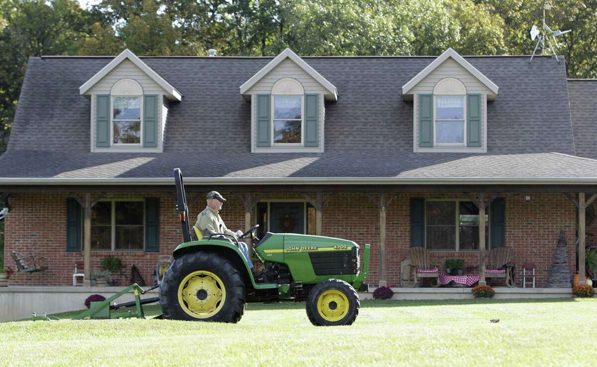 FILE - In this Oct. 11, 2014, file photo, Larry McKirahan mows his front yard in Rushylvania, Ohio. Freddie Mac reports on average U.S. mortgage rates, on Thursday, Jan. 29, 2015.