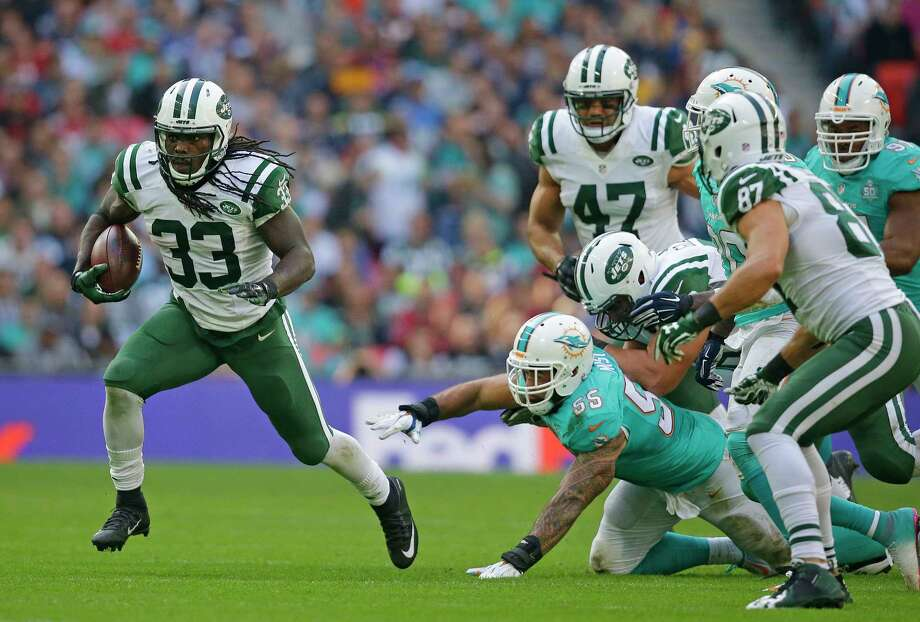 The Jets' Chris Ivory, left, runs with the ball during Sunday's game against the Dolphins at Wembley stadium in London. Photo: The Associated Press  / AP