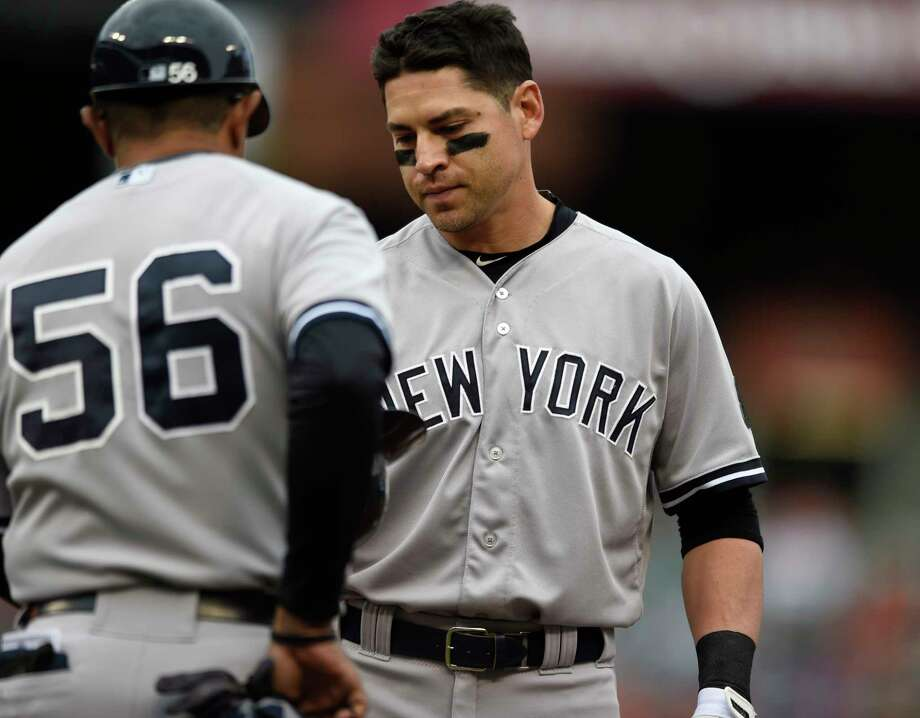 The Yankees' Jacoby Ellsbury, right, gives his helmet to first base coach Tony Pena after grounding out in the fourth inning Sunday. Photo: Gail Burton —  The Associated Press  / FR4095 AP