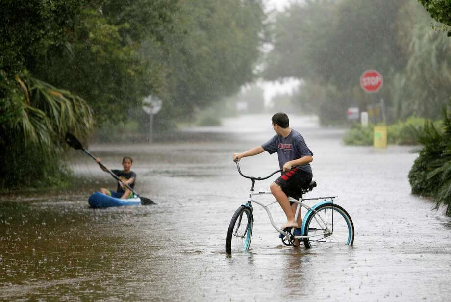 Will Cunningham, 14, rides his bike down Station 29 on Sullivan's Island, S.C., with his friend Patrick Kelly, 14, going the kayak route during flood waters on Sullivan's Island on Oct. 3, 2015. Rain pummeling parts of the East Coast showed little sign of slackening Saturday, with record-setting precipitation prolonging the soppy misery that has been eased only by news that powerful Hurricane Joaquin will not hit the U.S. Photo: AP Photo/Mic Smith  / FR2 AP