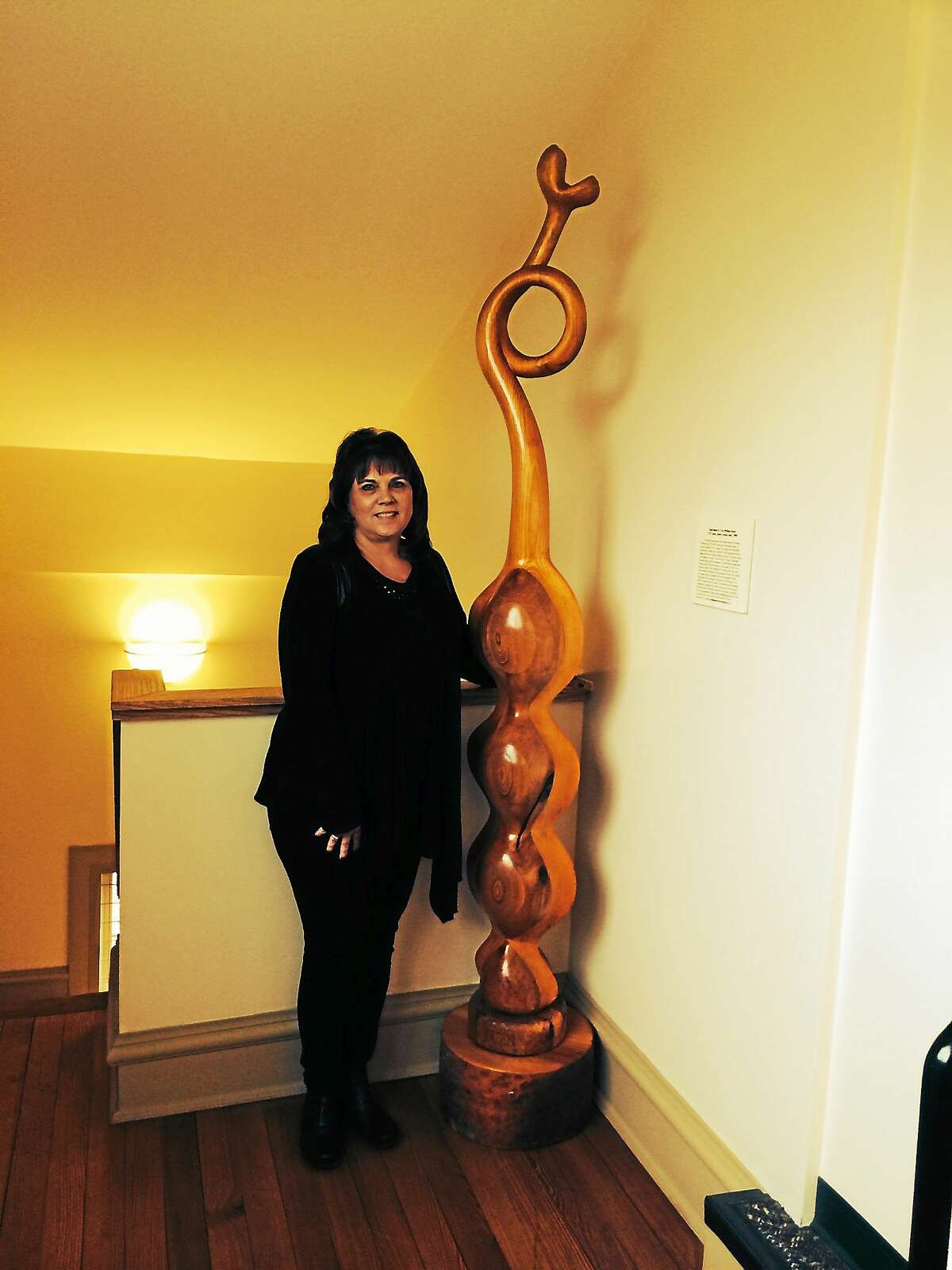 """Contributed photo William Kent's 7-foot-tall wood sculpture, """"Shell Bean # 14,"""" has just been installed on the third floor landing of Durham Town Hall. Above, First Selectman Laura Francis stands with the sculpture."""