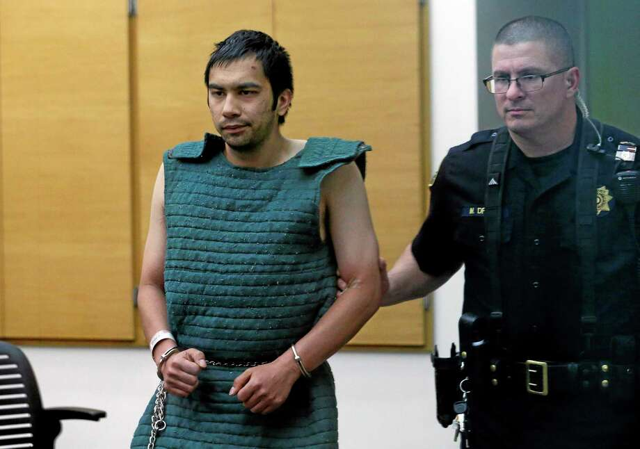 Shooting suspect Aaron Ybarra, left, is led in chains to a court hearing at a King County Jail courtroom Friday, June 6, 2014, in Seattle. Ybarra was arrested in the killing of a 19-year-old student and wounding of two other young people Thursday at Seattle Pacific University. Police say another student pepper-sprayed and tackled him. (AP Photo/Elaine Thompson) Photo: AP / AP