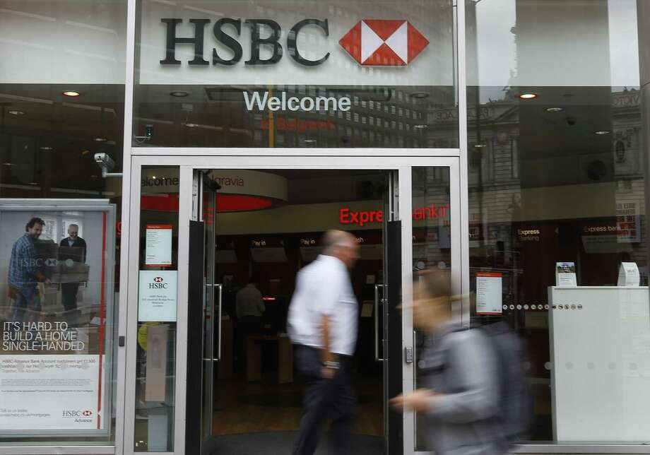 Pedestrians pass a branch of HSBC in London on June 9, 2015. HSBC Holdings, Britain's largest bank by market value, will cut between 22,000 and 25,000 jobs around the world in an attempt to reduce costs and shift its center of gravity back towards fast-growing Asian economies. Photo: AP Photo/Kirsty Wigglesworth  / AP