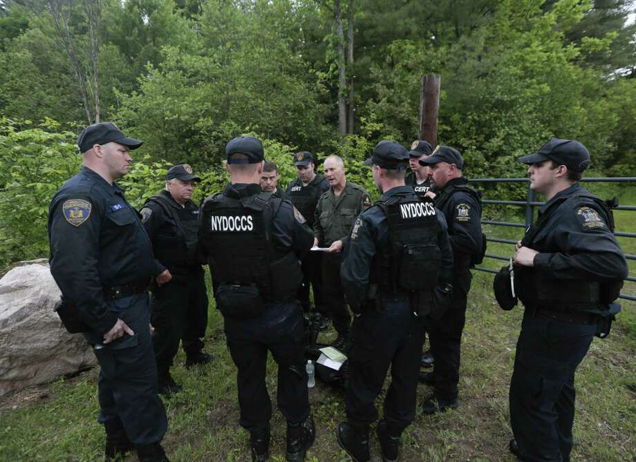 State forest ranger Dan Fox reviews a map with members of the New York State Department of Corrections and Community Supervision emergency response team before entering a wooded area in search of two prisoners who escaped from the Clinton Correctional Facility on Monday, June 8, 2015, in Dannemora, N.Y. The two murderers who escaped from the prison by cutting through steel walls and pipes remain on the loose Monday as authorities investigate how the inmates obtained the power tools used in the breakout. Photo: AP Photo/Mike Groll  / AP