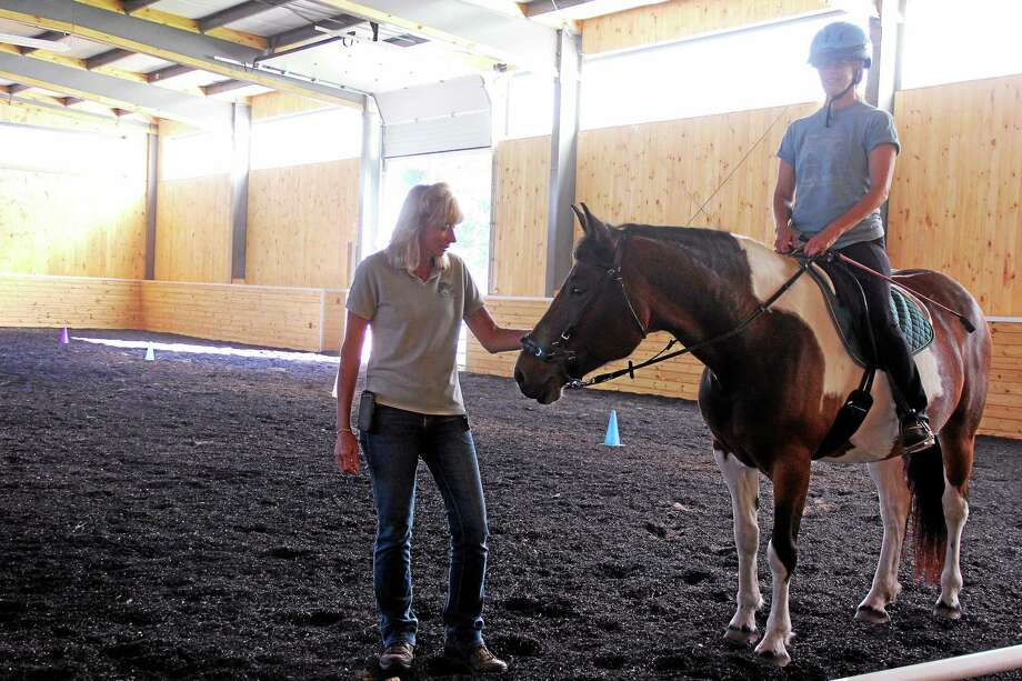 Manes & Motions Director Janice Anderson visits with instructor Janis Clifton and Bella inside the facility's new indoor arena in Middletown. The Mane Event fundraiser was held for the first time this year at Daniels Farm. Photo: Kathleen Schasssler - Middletown Press  / Kathleen Schassler All Rights