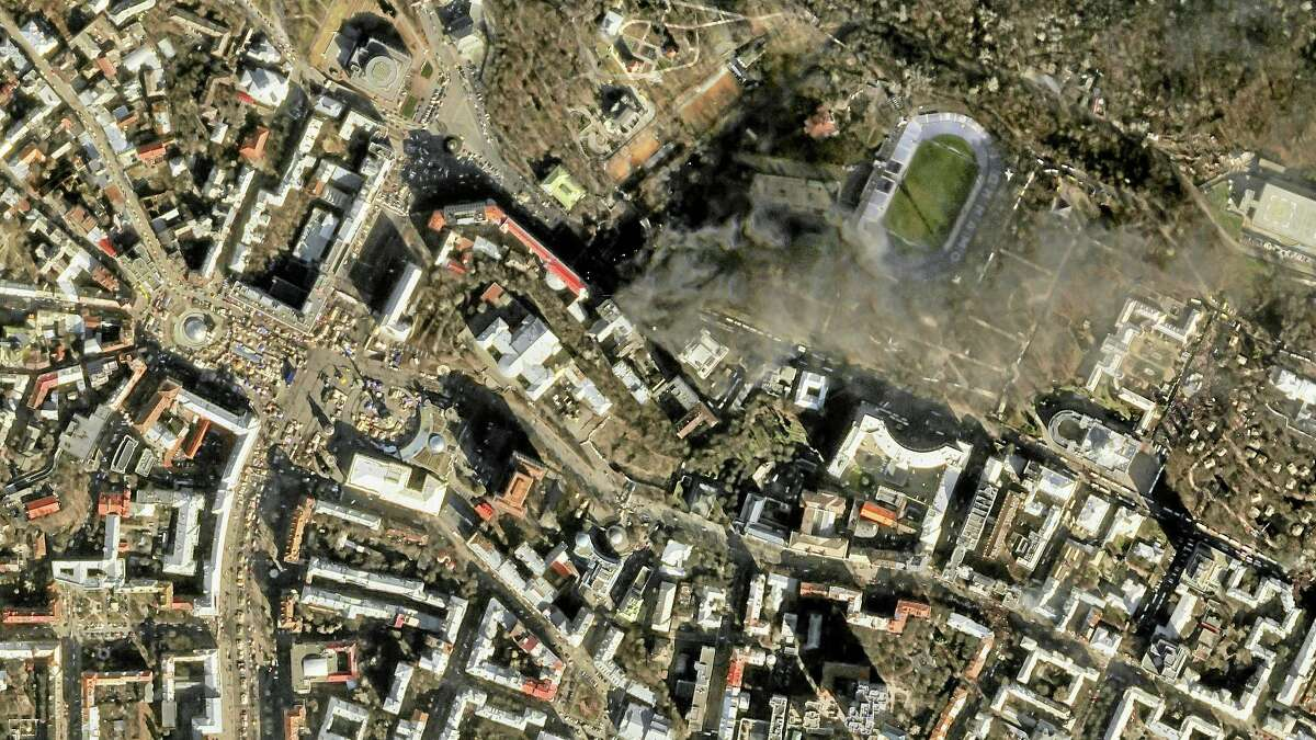 In this file satellite image provided by Skybox Imaging and taken by SkySat-1 on Feb. 18, smoke rises from the site of anti-government protests, upper center, in Kiev, Ukraine.