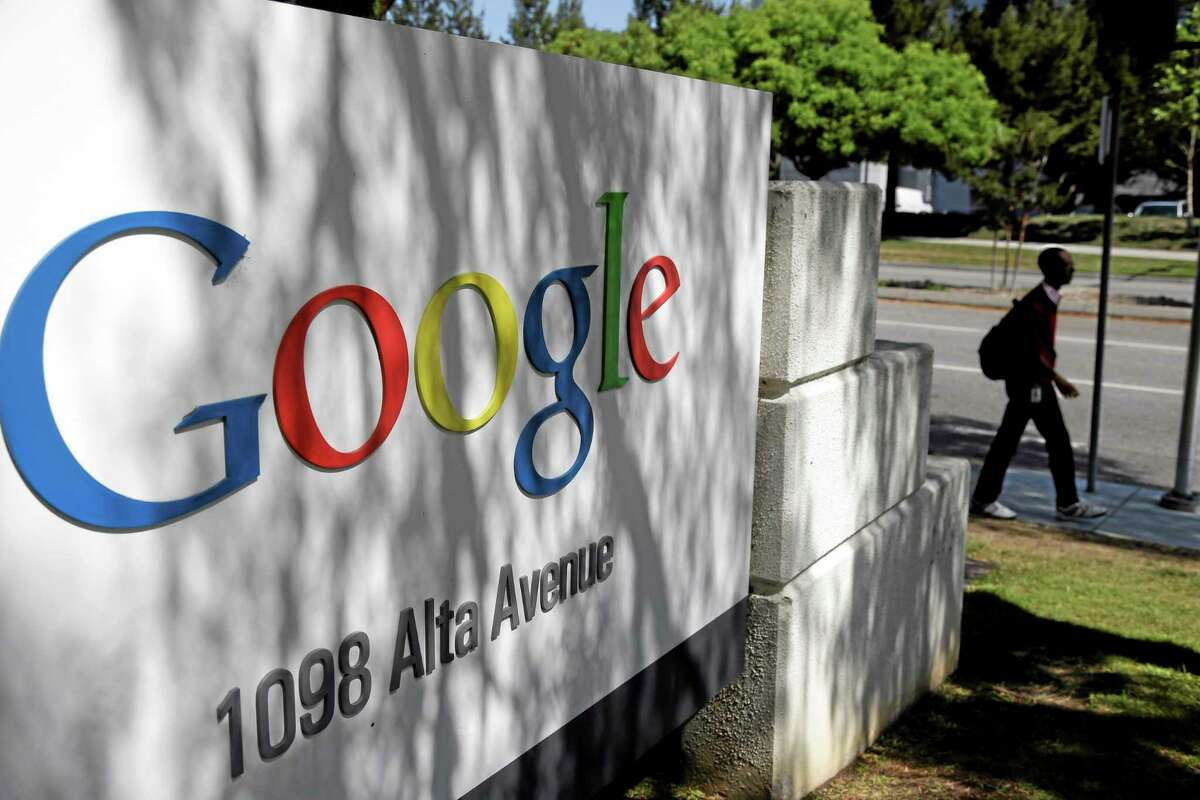 In this June 5 photo, a man walks past a Google sign at the company's headquarters in Mountain View, California.